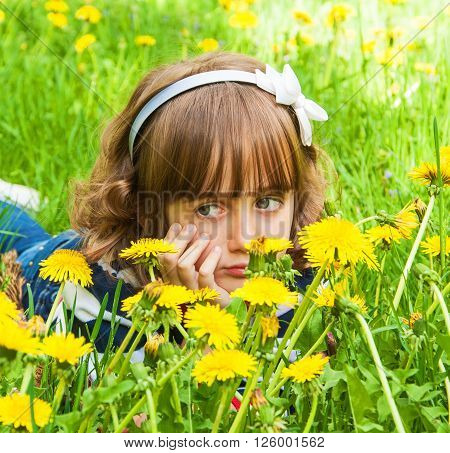 Portrait of sad little girl with big eyes in the meadow with dandelions