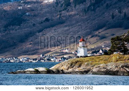 Small lighthouse on a cliff in a Norwegian fjord
