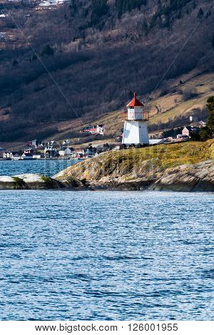 Small lighthouse in Norwegian fjord. Vertical composition