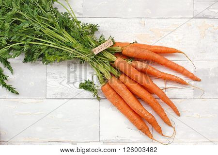 Carrot With Tha Label On The Wooden Background