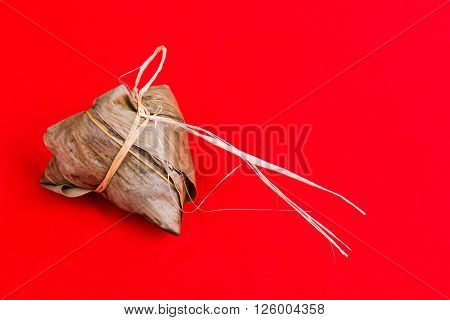 Fresh Chinese Rice Dumpling Or Zongzi Against Red Background