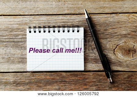 Notebook on a grey wooden background, close up, please call me