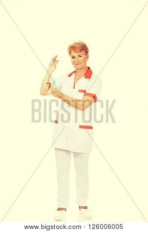 Smile elderly female doctor or nurse holds oxygen mask