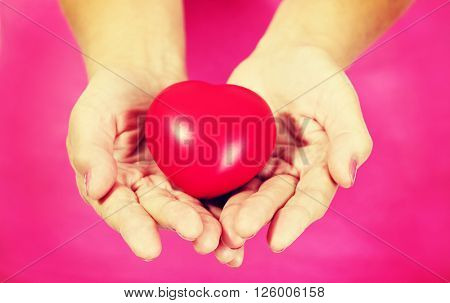 Old woman holding red toy heart