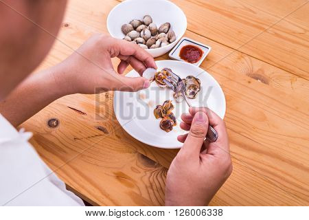 Person extracting cockles from its shell for consumption with chili dips. Delicacy among Asians.