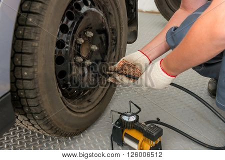 Mechanic Pump Inflates The The Wheel In Garage