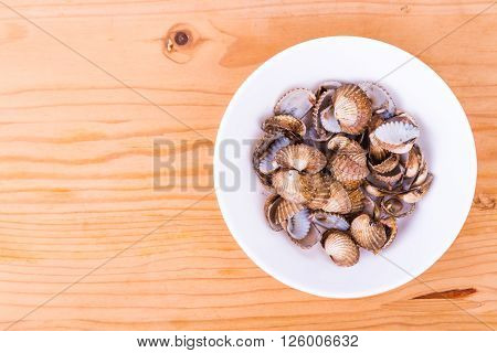 Empty cockles shells in bowl on wooden table from top down angle