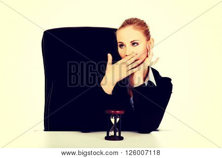 Yawning business woman with hourglass on the desk