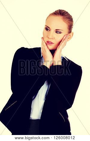 Young worried business woman with hands on cheeks