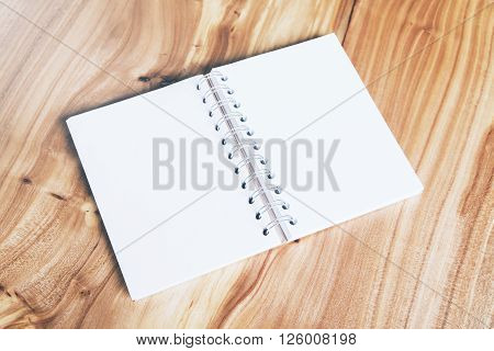 Blank white notepad on wooden tabletop, close up
