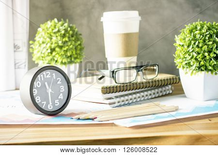 Designer desktop with black clock plants glasses and other items