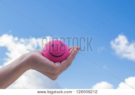 Hand holding a pink smily ball with sky background