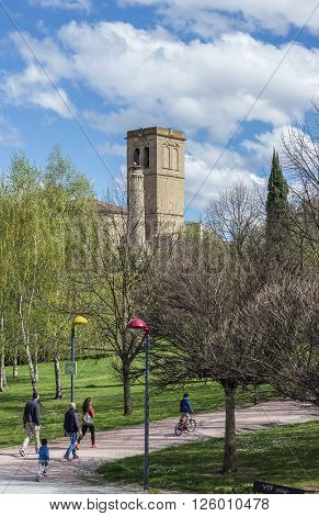 Logroño Spain - April 10 2016. A family walking in Park of the river Ebro with bellower of Santiago el Real church. Logroño La Rioja. Spain.