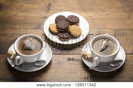 Serving and brewing tea.Set of two ceramic tea mugs with teabags and plates of cookies.