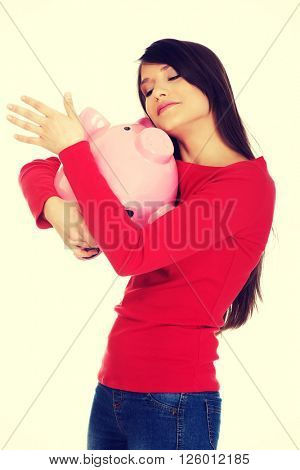 Happy young woman with piggybank.