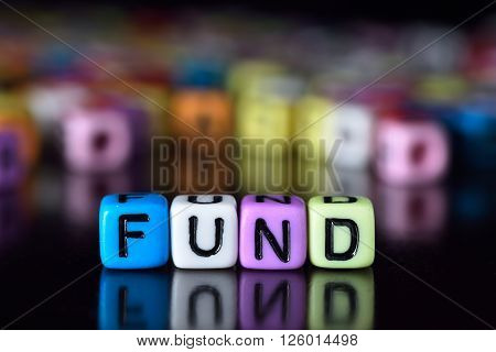 Fund word on colorful dice with reflection