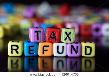 Tax refund word on colorful dice with reflection