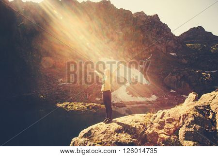 Woman Traveler meditating yoga relaxing alone standing on cliff sun light Travel healthy Lifestyle concept lake and rocky mountains landscape on background outdoor