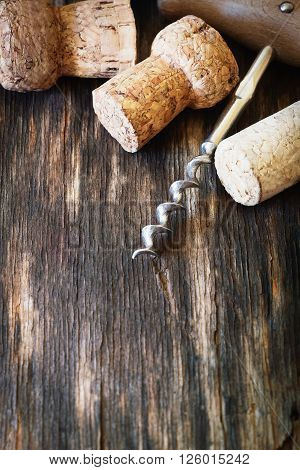 Old corkscrew for wine and wine corks on a vintage wooden background. Close-up. Toned image. Selective focus. Copy space background