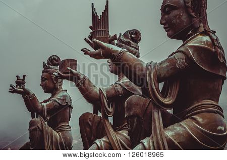 Buddhist statues praising and making offerings to the Tian Tan Buddha. The Po Lin Monastery and the Lantau Peak in the background, in Hong Kong. Hong Kong is popular tourist destination of Asia.