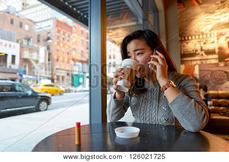 NEW YORK - CIRCA MARCH 2016: woman in Starbucks Cafe. Starbucks Corporation is an American global coffee company and coffeehouse chain based in Seattle, Washington