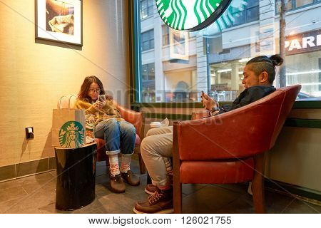 NEW YORK - CIRCA MARCH 2016: people in Starbucks Cafe. Starbucks Corporation is an American global coffee company and coffeehouse chain based in Seattle, Washington