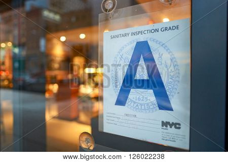 NEW YORK - CIRCA MARCH 2016: close up shot of sanitary inspection grade on the window of Starbucks Cafe. Starbucks Corporation is an American global coffee company and coffeehouse chain.