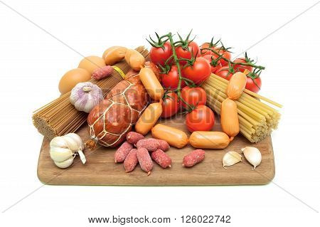 pasta vegetables and sausages on a cutting board. white background - horizontal photo.