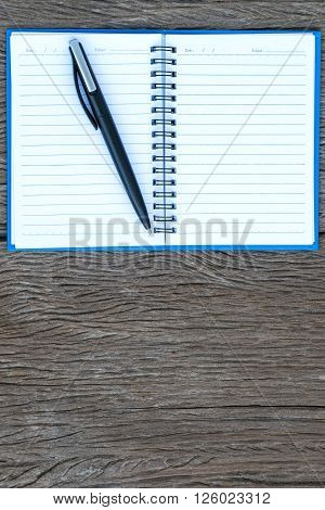 Place the pen on a blank page of a notebook on old wooden background.