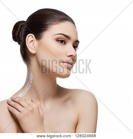 Beautiful young woman applying moisturizing cream to neck and shoulder. Isolated over white background. Copy space. Square composition.