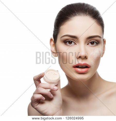 Beautiful young woman holding jar with loose powder near face. Isolated over white background. Copy space. Square composition.