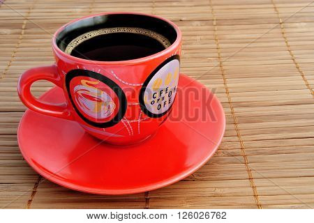 Cup of coffee with a saucer on a horizontal surface. The cup and a saucer are located at the left. Indoors. Daylight. Horizontal format. Photo. Color.