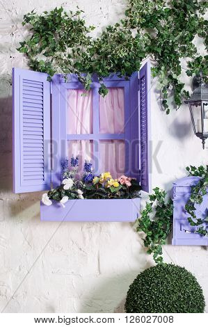 Pretty small purple window and box with flowers in an old house.
