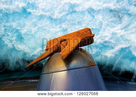 Heavy rusty anchor against sea water splashes background.