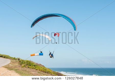 PORT ELIZABETH SOUTH AFRICA - FEBRUARY 27 2016: Three paragliders in the air next to a windsock at Beachview near Port Elizabeth