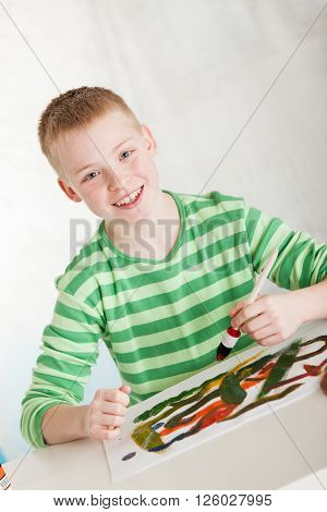 Slanted View Of Smiling Boy With Paint Brush