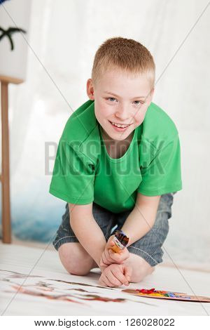 Smiling Boy In Green Shirt And Jean Shorts Paints
