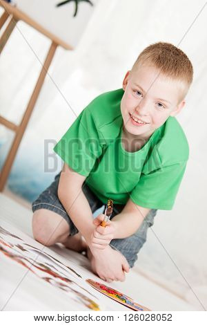 Slanted View Of Boy Kneeling On Painting