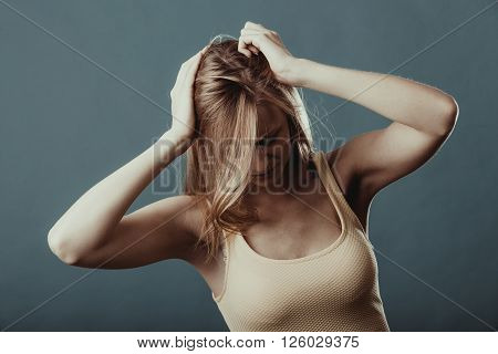 Negative human emotions facial expressions reaction attitude. Closeup stressed worried young woman having really bad headache hurt pain holding head with hands on blue gray