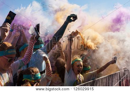 HAMPTON, GA - APRIL 2016:  A crowd of runners who completed the Color Run toss packets of colored corn starch into the air creating an organic explosion of colors over the group in Hampton GA on April 2 2016.