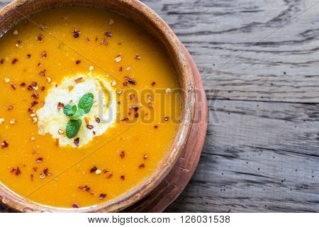 Bowl of spicy pumpkin soup on the wooden table