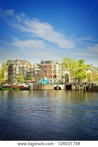 Old houses of  Amsterdam on Amstel river, Holland, retro toned