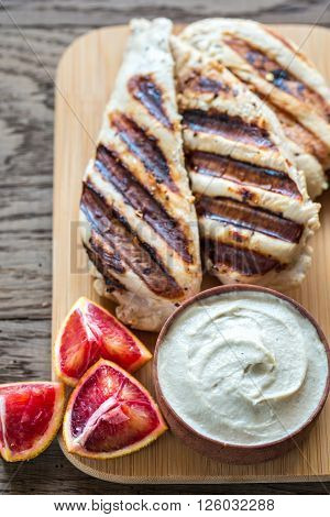 Grilled Chicken With Tahini Sauce On The Wooden Board