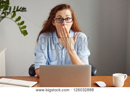 Young Attractive Office Worker Looking At The Camera In Surprise. Portrait Of Pretty Woman In Glasse
