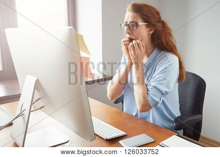 Stressed Shocked Businesswoman Sitting At The Table In Front Of Computer In The Office Looking Stunn