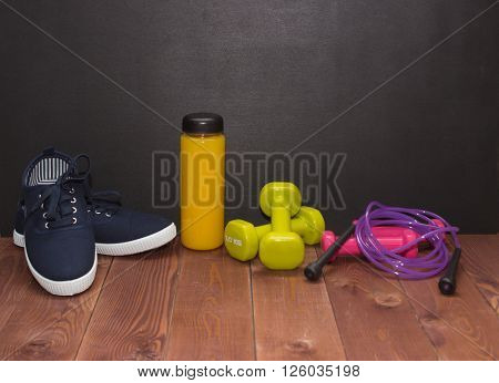 Fitness Shoes, Dumbbells And Bottle Of Juice On Wooden Floor