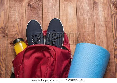 Backpack With Sports Equipment On Wooden Floor