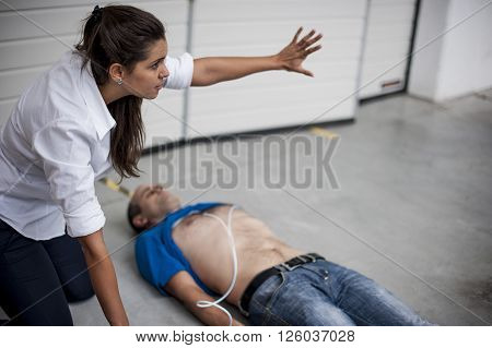 A rescuer assisting an unconscious man after a fatal accident