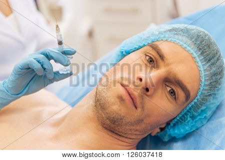 Portrait of handsome young man looking at camera and waiting for an injection. Doctor is holding a syringe