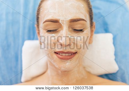 Top view of beautiful young woman getting face skin treatment lying with cream on her face